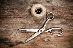老剪刀和丝球黄麻在木桌上 免版税库存图片