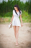 有短的白色礼服的可爱的深色的女孩赤足漫步在乡下路的 新美好妇女走 免版税库存照片