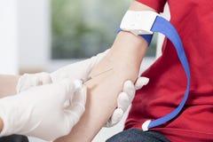 Χέρια νοσοκόμας που παίρνουν το δείγμα αίματος Στοκ Φωτογραφίες