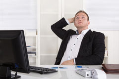 坐在书桌的沉思年轻作的商人查寻 免版税库存图片