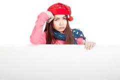 有红色圣诞节帽子的亚裔女孩在与空白的标志的坏心情 库存照片