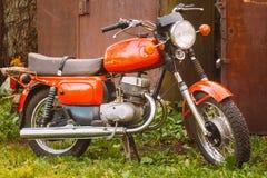 葡萄酒红色摩托车普通摩托车在乡下 免版税库存照片