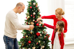 Χαμογελώντας οικογένεια που διακοσμεί το χριστουγεννιάτικο δέντρο στο σπίτι Στοκ εικόνα με δικαίωμα ελεύθερης χρήσης