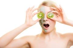 прикладывать политуру кожи внимательности прозрачную Женщина в маске глины с кивиом на стороне Стоковые Фото