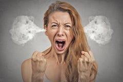 从耳朵出来的恼怒的少妇蒸汽尖叫 免版税库存照片