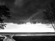 会集在海滩的邪恶的暴风云 免版税图库摄影