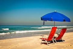 Έδρες και ομπρέλα στην παραλία Στοκ Φωτογραφίες