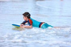 在识别不明飞机委员会的男孩游泳 免版税库存图片