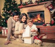 在壁炉附近的家庭在圣诞节装饰了房子 免版税图库摄影