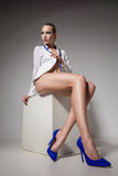 坐在时髦鞋子的美丽的少妇 免版税库存图片