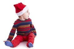有看起来圣诞老人的盖帽的男婴惊奇在右边 免版税库存照片