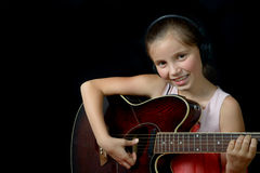 弹吉他的一个相当小女孩 免版税库存图片