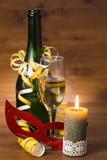 与香槟瓶、玻璃和燃烧的蜡烛的新年静物画 免版税库存图片