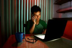 青少年使用一个手机或智能手机在便携式计算机前面 图库摄影