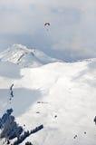 在积雪的山上的滑翔伞在阿尔卑斯 库存照片
