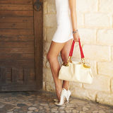 Το θηλυκό πετάλωσε τα άσπρα υψηλά παπούτσια τακουνιών κρατώντας σε μια τσάντα μόδας χεριών Στοκ Φωτογραφία