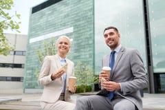 Χαμογελώντας επιχειρηματίες με τα φλυτζάνια εγγράφου υπαίθρια Στοκ φωτογραφία με δικαίωμα ελεύθερης χρήσης