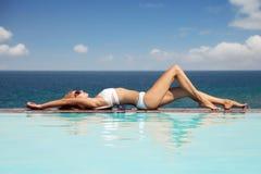 晒日光浴美丽的妇女 从游泳池的好的海视图 免版税图库摄影