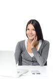 Женщина сидя смотрящ ее портативный компьютер Стоковые Фотографии RF