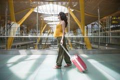 在机场里面的怀孕的拉扯的手提箱 免版税库存图片