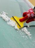妇女刮的冰的手从汽车挡风玻璃的 库存图片