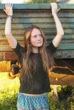 站立在老卡车附近的年轻逗人喜爱的女孩 帮助在庭院里 免版税图库摄影