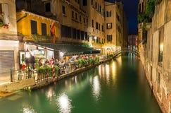 运河和餐馆夜视图在威尼斯 库存照片