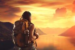 远足有背包的女孩看日落 免版税图库摄影