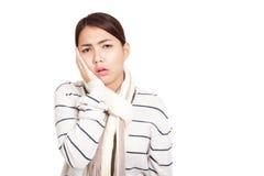 有围巾的美丽的亚裔女孩得到了牙痛 免版税图库摄影