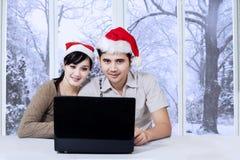 使用膝上型计算机的夫妇在冬日 免版税图库摄影