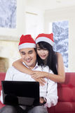 使用膝上型计算机的愉快的夫妇购买的在网上 免版税图库摄影