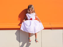 街道时尚孩子,礼服的小女孩在五颜六色的墙壁附近 免版税库存照片