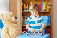 在家使用与片剂计算机的可爱的孩子在他的屋子里 免版税图库摄影