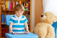 在家使用与片剂计算机的小孩男孩在他的屋子里 图库摄影
