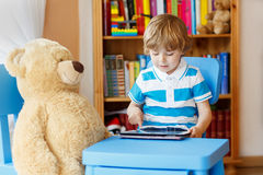 在家使用与片剂计算机的小孩男孩在他的屋子里 免版税图库摄影
