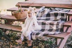 坐在湖附近的小女孩在秋天前面 库存图片