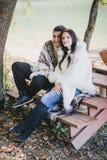坐在湖附近的愉快的夫妇在秋天森林里 免版税库存图片