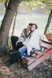 坐在湖附近的愉快的夫妇在秋天森林里 免版税库存照片