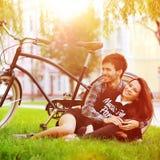 在公园的愉快的微笑的年轻夫妇在葡萄酒附近骑自行车 免版税库存图片
