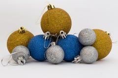 银、金子和蓝色发光的圣诞节球在白色背景 库存图片