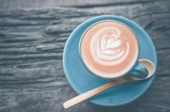 拿铁艺术,在木背景的蓝色咖啡杯 免版税库存照片
