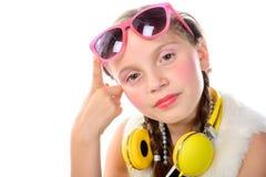 Ένα όμορφο μικρό κορίτσι με τα ρόδινα γυαλιά και τα κίτρινα ακουστικά Στοκ Φωτογραφία