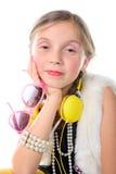 Ένα όμορφο μικρό κορίτσι με τα ρόδινα γυαλιά και τα κίτρινα ακουστικά Στοκ Εικόνες