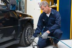Μηχανικός που ελέγχει την πίεση ελαστικών αυτοκινήτου Στοκ Εικόνα