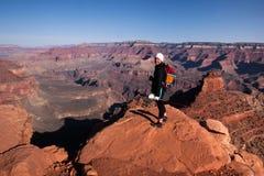 站立在峭壁的一个女性远足者在大峡谷 免版税库存图片
