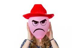 拿着有恼怒的面孔和红色帽子的女孩桃红色气球 库存照片