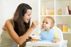 用匙喂她的婴孩的母亲 免版税图库摄影