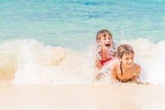 Δύο νέα ευτυχή παιδιά - κορίτσι και αγόρι - που έχουν τη διασκέδαση στο νερό, τ Στοκ φωτογραφία με δικαίωμα ελεύθερης χρήσης