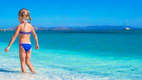 热带海滩的可爱的小女孩在期间 库存照片