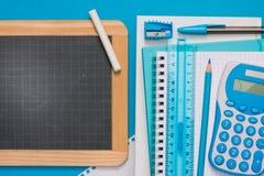 黑板和文具在蓝色背景 库存照片